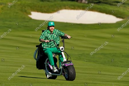Macklemore rides his golf cart down the first fairway during the charity challenge event of the AT&T Pebble Beach Pro-Am golf tournament, in Pebble Beach, Calif