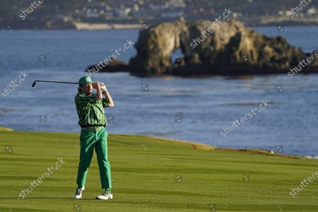 Stock Picture of Macklemore watches his shot from the 18th fairway during the charity challenge event of the AT&T Pebble Beach Pro-Am golf tournament, in Pebble Beach, Calif