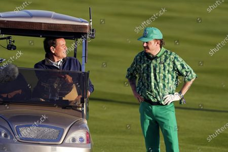 Stock Image of Macklemore, right, talks with Jim Nantz on the 18th fairway during the charity challenge event of the AT&T Pebble Beach Pro-Am golf tournament, in Pebble Beach, Calif