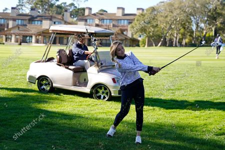 Stock Photo of Kira K. Dixon hits from off the first fairway as Jim Nantz looks on during the charity challenge event of the AT&T Pebble Beach Pro-Am golf tournament, in Pebble Beach, Calif