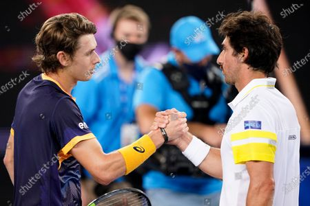 Stock Picture of Alex de Minaur (L) of Australia shakes hands with Pablo Cuevas of Uruguay following their second Round Men's singles match on Day 4 of the Australian Open Grand Slam tennis tournament at Melbourne Park in Melbourne, Australia, 11 February 2021.