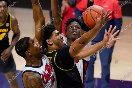 Missouri guard Mark Smith (13) attempts a layup between Mississippi guards Luis Rodriguez, left, and Jarkel Joiner during the first half of an NCAA college basketball game in Oxford, Miss