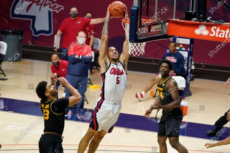 Mississippi forward KJ Buffen (5) dunks between Missouri guard Mark Smith (13) and forward Kobe Brown (24) during the second half of an NCAA college basketball game in Oxford, Miss