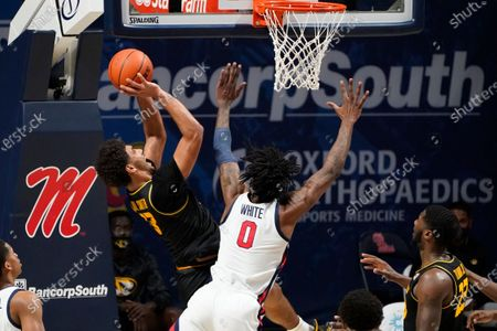 Missouri guard Mark Smith (13) attempts a shot while Mississippi forward Romello White (0) defends during the second half of an NCAA college basketball game in Oxford, Miss., . Mississippi won 80-59