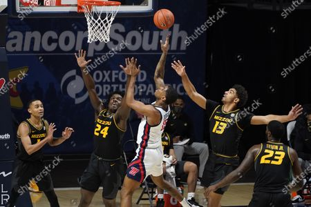 Mississippi guard Luis Rodriguez (15) attempts a shot while Missouri forward Kobe Brown (24) and guard Mark Smith (13) defend during the first half of an NCAA college basketball game in Oxford, Miss., . Mississippi won 80-59
