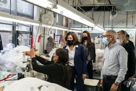 LG Kathy Hochul visits Four Seasons Fashion as part of women-owned nonprofit Garment District for Gowns on 39th street of Manhattan. LG was touring Four Season Fashion company owned by Tony Singh (R). LG observes how seamstress works on sewing gown. Nonprofit organization helped already to manufacture more than 300,000 PPE and sent them to New York State hospitals.