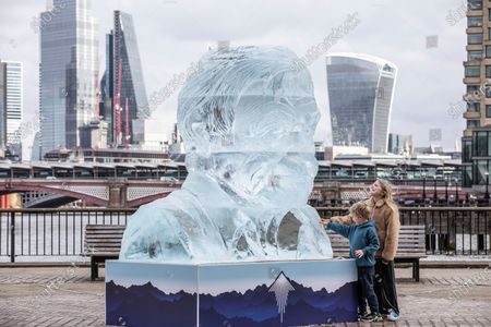 Cooco Bennett (10) and brother Frank Bennet (5) admire the giant ice sculpture of Sir David Attenborough that will stand on the Southbank in the centre of London to demonstrate the Arctic ice melt caused by one UK person EVERY FORTNIGHT.