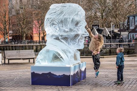 Stock Picture of Cooco Bennett (10) and brother Frank Bennet (5) admire the giant ice sculpture of Sir David Attenborough that will stand on the Southbank in the centre of London to demonstrate the Arctic ice melt caused by one UK person EVERY FORTNIGHT.