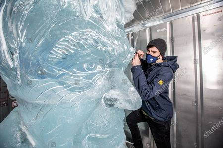 Sam Swanborough of Hamilton Sculptors makes final touches to 'TENZING Take Action' ice sculpture of Sir David Attenborough, to demonstrate the Arctic ice melt caused by one UK person EVERY FORTNIGHT, launching on Wednesday 10th February 2021 at Southbank Observation Point, London, England. UKTENZING is installing a giant 5m 3 ice sculpture of Sir David Attenborough in the centre of London to demonstrate the Arctic ice melt caused by one UK person each fortnight. The installation marks the launch of TENZING's sustainability campaign, Take Action, a carbon management plan that provides people with accessible and measurable tools to helpmake environmental changes, from 'personalised' carbon footprint calculator to making its community carbon neutral.