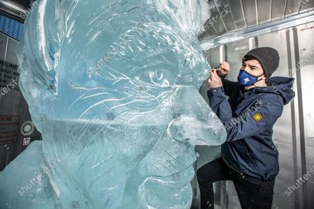 Sam Swanborough of Hamilton Sculptors makes final touches to 'TENZING Take Action' ice sculpture of Sir David Attenborough, to demonstrate the Arctic ice melt caused by one UK person EVERY FORTNIGHT, launching on Wednesday 10th February 2021 at Southbank Observation Point, London, England. UKTENZING is installing a giant 5m 3 ice sculpture of Sir David Attenborough in the centre of London to demonstrate the Arctic ice melt caused by one UK person each fortnight. The installation marks the launch of TENZING's sustainability campaign, Take Action, a carbon management plan that provides people with accessible and measurable tools to helpmake environmental changes, from a personalised carbon footprint calculator to making its community carbon neutral.