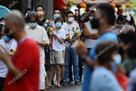 Devotees wearing protective mask queue to enter the Kwan Im Thong Hood Cho temple to offer prayers to seek blessings from the Goddess of Mercy as Singapore prepares to usher in the Lunar New Year amid the COVID-19 pandemic on February 11, 2021 in Singapore. The government has introduced a capped of 8 unique visitors per household per day and a maximum visit of 2 households daily to minimise the spread of the COVID-19 pandemic. On February 12, people around the world will welcome the Year of the Ox, one of the most anticipated holidays on the Chinese calendar.