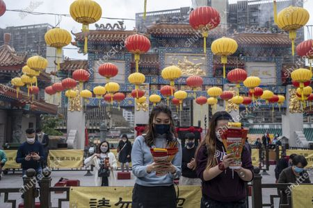 People wearing face mask pray inside Wong Tai Sin Temple. The Lunar New Year will mark the year of the Ox in the Chinese Zodiac Calendar.