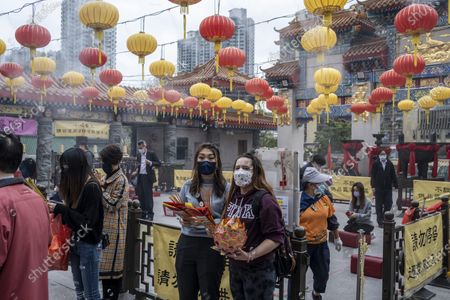 People are seen praying inside Wong Tai Sin Temple. The Lunar New Year will mark the year of the Ox in the Chinese Zodiac Calendar.