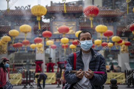 A Man holding a insect stick Parys inside Wong Tai Sin Temple. The Lunar New Year will mark the year of the Ox in the Chinese Zodiac Calendar.