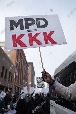A protester holds a sign critical of the Minneapolis Police Department, on January 9, 2021 in Minneapolis, United States. Hundreds of Black Lives Matter protesters and families members of Dolal Idd gathered in downtown Minneapolis, MN to protest the police killing of Dolal Idd during a sting operation. Protesters also spoke out against the decision by the Kenosha County district attorney not to charge Rusten Sheskey, the officer who shot Jacob Blake seven times in the back.