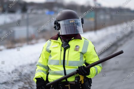 A State Patrol officer stands in front of a freeway exit in St. Paul to block marchers on Martin Luther King Jr. Day. January 18, 2021.