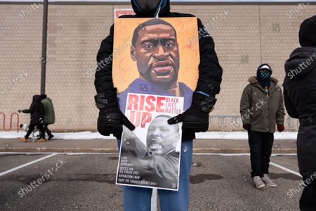 A protester holds a poster of George Floyd during a rally in St. Paul on Martin Luther King Jr. Day. January 18, 2021.