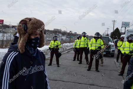 A man walks past State Patrol officers as they block a freeway exit in St. Paul on Martin Luther King Jr. Day. January 18, 2021.