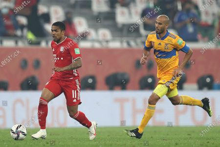 Bayern's Douglas Costa, left, runs with the ball past Tigres' Guido Pizarro during the Club World Cup final soccer match between FC Bayern Munich and Tigres at the Education City stadium in Al Rayyan, Qatar