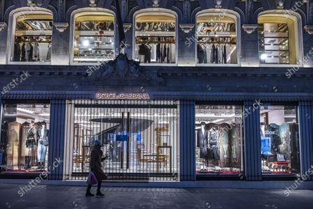 A lady walking past the Dolce & Gabbana stores in London, during the third nationwide lockdown.  Dolce & Gabbana is an Italian luxury fashion house founded in 1985 in Legnano by Italian designers Domenico Dolce and Stefano Gabbana.