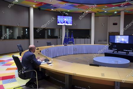 European Council President Charles Michel, left, talks to Eurogroup President Paschal Donohoe, right on the screen, during a video conference meeting with inter-institutional actors at the European Council headquarters in Brussels