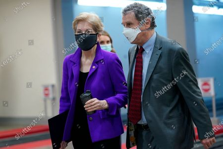 Sen. Elizabeth Warren, D-Mass., left, and Sen. Sherrod Brown, D-Ohio, right, walk on Capitol Hill in Washington, before the start of the third day of the second impeachment trial of former President Donald Trump