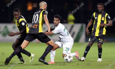 Al-Ahli's player Abdulrahman Ghareeb (2-R) in action against Al-Ittihad's Fahad Al Muwallad (R), Saud Abdulhamid (L) and Karim El Ahmadi (2-L) during the Saudi Professional League soccer match between Al-Ahli and Al-Ittihad at King Abdullah Sport City Stadium, 30 kilometers north of Jeddah, Saudi Arabia, 11 February 2021.