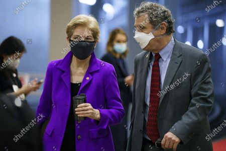 Stock Photo of Senator Elizabeth Warren, a Democrat from Massachusetts, and Senator Sherrod Brown, a Democrat from Ohio, wearing protective masks while walking through the Senate Subway at the U.S. Capitol on the third day of the second impeachment trial at the Capitol in Washington, DC on Thursday, February 11, 2021. Arguments will be presented in the impeachment trial of former President Donald Trump today.