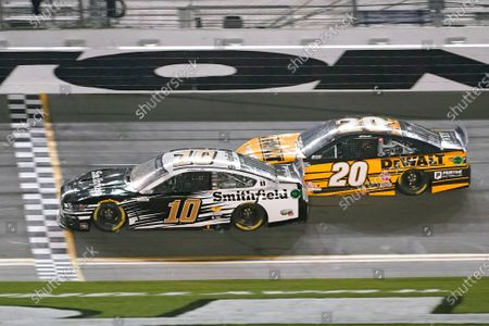 Aric Almirola (10) crosses the finish line ahead of Christopher Bell (20) to win the first of two qualifying auto races for the NASCAR Daytona 500 at Daytona International Speedway, in Daytona Beach, Fla