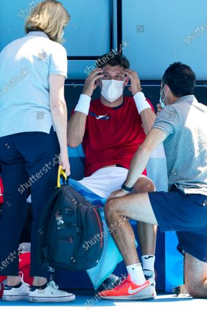Pablo Carreno Busta of Spain receives medical attention during a break in action against Grigor Dimitrov of Bulgaria during their third round match of the Australian Open grand slam tennis tournament at Melbourne Park in Melbourne, Australia, 12 February 2021.