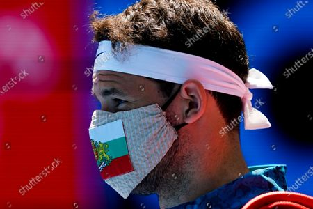 Grigor Dimitrov of Bulgaria arrives wearing a face mask ahead of action against Pablo Carreno Busta of Spain during their third round match of the Australian Open grand slam tennis tournament at Melbourne Park in Melbourne, Australia, 12 February 2021.