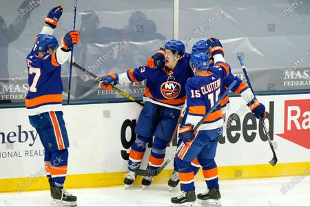 Stock Picture of Teammates flock to congratulate New York Islanders center Mathew Barzal (13) after Barzal scored a goal during the third period of an NHL hockey game, in Uniondale, N.Y. From left are Islanders center Anders Lee (27), Barzal, right wing Cal Clutterbuck (15) and defenseman Ryan Pulock (6
