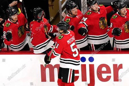 Chicago Blackhawks defender Ian Mitchell (51) celebrates with teammates after scoring a goal against the Columbus Blue Jackets during the second period of an NHL hockey game in Chicago