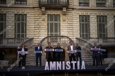 """Stock Photo of Catalan leaders imprisoned for their role in the 2017 push for an independent Catalan republic, Carme Forcadell, Joaquim Forn, Raül Romeva, Jordi Sanchez, Jordi Cuixart, Oriol Junqueras, Josep Rull, Jordi Turull and Dolors Bassa, from left to right, pose for a photo holding banners reading """"Amnesty"""" during a campaign event in Barcelona, Spain, on . Over five million voters will be called to the polls on Sunday in Spain's northeast Catalonia for an election that will measure the impact of the coronavirus pandemic on the restive region's secessionist movement"""