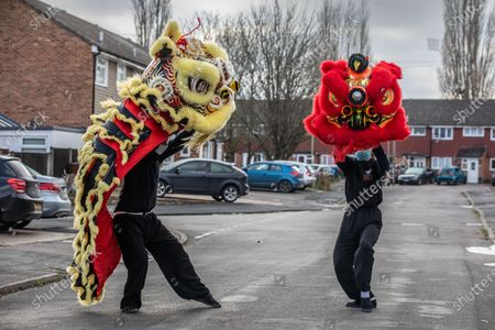 Stock Picture of Chinese New Year: Lion Dance Instructor Matt Williams from the World Eagle Claw Association UK gives his costumes an airing with Greg Currie in the street in Hampshire over the Chinese New Year after all his bookings and performances have been cancelled due to the current Coronavirus Lockdown during the Year of the Ox festivities.