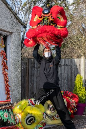 Chinese New Year: Lion Dance Instructor Matt Williams from the World Eagle Claw Association UK gives his costumes an airing in his back yard in Hampshire over the Chinese New Year after all his bookings and performances have been cancelled due to the current Coronavirus Lockdown during the Year of the Ox festivities.