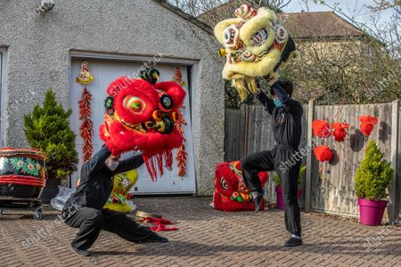 Chinese New Year: Lion Dance Instructor Matt Williams from the World Eagle Claw Association UK gives his costumes an airing with Greg Currie in back yard in Hampshire over the Chinese New Year after all his bookings and performances have been cancelled due to the current Coronavirus Lockdown during the Year of the Ox festivities.