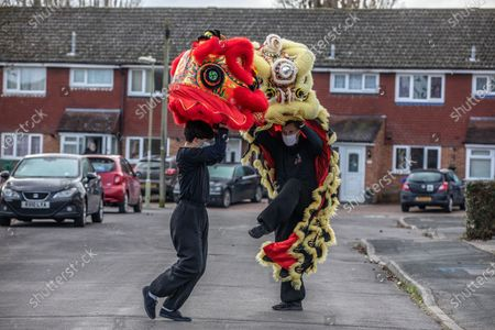 Chinese New Year: Lion Dance Instructor Matt Williams from the World Eagle Claw Association UK gives his costumes an airing with Greg Currie in the street in Hampshire over the Chinese New Year after all his bookings and performances have been cancelled due to the current Coronavirus Lockdown during the Year of the Ox festivities.