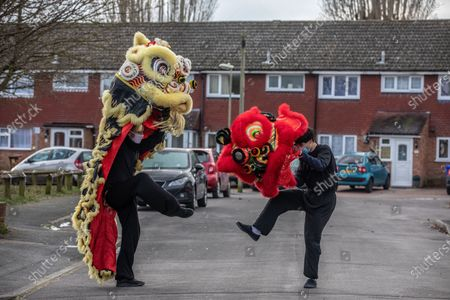 Stock Photo of Chinese New Year: Lion Dance Instructor Matt Williams from the World Eagle Claw Association UK gives his costumes an airing with Greg Currie in the street in Hampshire over the Chinese New Year after all his bookings and performances have been cancelled due to the current Coronavirus Lockdown during the Year of the Ox festivities.