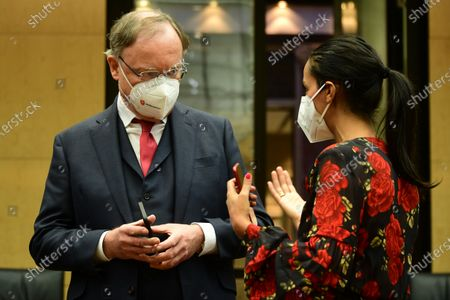 Stock Photo of Lower Saxony State Premier Stephan Weil (L) and Berlin state secretary Sawsan Chebli  wear face masks as they talk prior to the beginning of the 1,000th session of the German Federal Council (Bundesrat), in Berlin, Germany, 12 February 2021. The German Federal Council assembled for the 1,000th time. The first session was held on 07 September 1949.