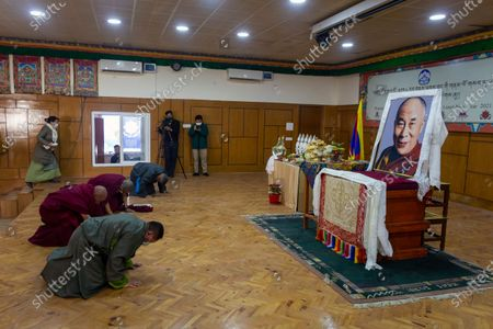 Exile Tibetan parliamentarians prostrate in front of a portrait of their spiritual leader the Dalai Lama at an event marking the first day of the Tibetan New Year or Losar in Dharmsala, India