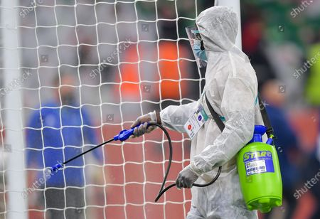 Sanitation worker sprays disinfectants on the goal during the FIFA Club World Cup 3rd place match between Egypt's Al Ahly SC and Brazil's SE Palmeiras at the Education City Stadium in Doha, Qatar, Feb. 11, 2021.