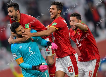 Al Ahly SC's goalkeeper Mohamed El-Shenawy (below L) and teammate Ayman Ashraf (above L), Mohamed Sherif (2nd R) celebrate after winning the penalty shoot-out of the FIFA Club World Cup 3rd place match between Egypt's Al Ahly SC and Brazil's SE Palmeiras at the Education City Stadium in Doha, Qatar, Feb. 11, 2021.