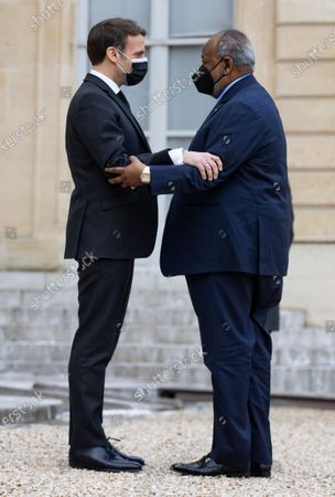 French President Emmanuel Macron (L) greets President of Djibouti Ismail Omar Guelleh (R) as he arrives for a meeting and lunch at the Elysee Palace in Paris, France, 12 February 2021.