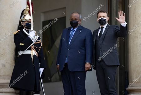 French President Emmanuel Macron (R) greets President of Djibouti Ismail Omar Guelleh (C) as he arrives for a meeting and lunch at the Elysee Palace in Paris, France, 12 February 2021.