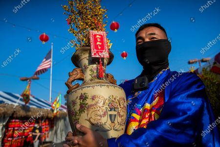 """Wearing the ao dai, a traditional Vietnamese dress outfit, Jimmy Huynh, greets people while selling a li xi, or red envelope where a monetary gift is given during holidays, attached to a vase of Hoa Mai flowers in preparation for the Lunar New Year at the Asian Garden Mall in Little Saigon, Westminster Wednesday, Feb. 10, 2021. For those who celebrate Lunar New Year, which starts Friday, Feb. 12, COVID has forced them to avoid touching cash and stuff traditional red envelopes normally filled with """"lucky"""" money instead with checks, Lotto tickets, gift cards and the like. It will be the Year of the Ox. People flocked to Little Saigon to purchase holiday wares, traditional Vietnamese outfits, baked goods or flowers set up at store entrances or along the sidewalk.(Allen J. Schaben / Los Angeles Times)"""