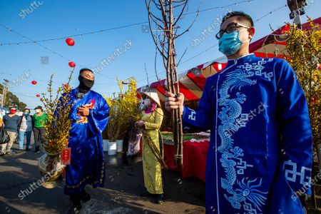 """Stock Image of All wearing the ao dai, a traditional Vietnamese dress outfit, Jimmy Huynh, left, greet people while selling a li xi, or red envelope where a monetary gift is given during holidays, attached to a vase of Hoa Mai flowers as Stephanie Vu, center, and Dang Nguyen sell flowers in preparation for the Lunar New Year at the Asian Garden Mall in Little Saigon, Westminster Wednesday, Feb. 10, 2021. For those who celebrate Lunar New Year, which starts Friday, Feb. 12, COVID has forced them to avoid touching cash and stuff traditional red envelopes normally filled with """"lucky"""" money instead with checks, Lotto tickets, gift cards and the like. It will be the Year of the Ox. People flocked to Little Saigon to purchase holiday wares, traditional Vietnamese outfits, baked goods or flowers set up at store entrances or along the sidewalk.(Allen J. Schaben / Los Angeles Times)"""