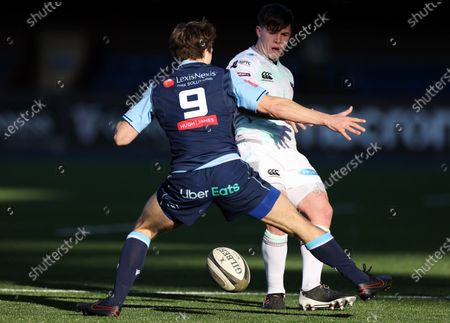 Callum Carson of Ospreys chips the ball past Jamie Hill of Cardiff Blues.