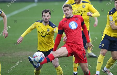 Scott Wootton of Wigan Athletic controls in the opposition area Anthony Forde of Oxford United is left