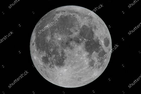 Stock Photo of Bright and beautiful full moon illumination in the dark night sky the traditionally known Beaver Moon, as seen from Eindhoven, a city in mainland Europe. The Moon or Luna or Selene is an astronomical body, the natural satellite of Earth, orbiting around the planet.